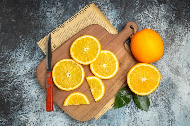 灰色の背景の新聞の木製まな板にナイフで新鮮なレモンスライスの水平方向のビュー