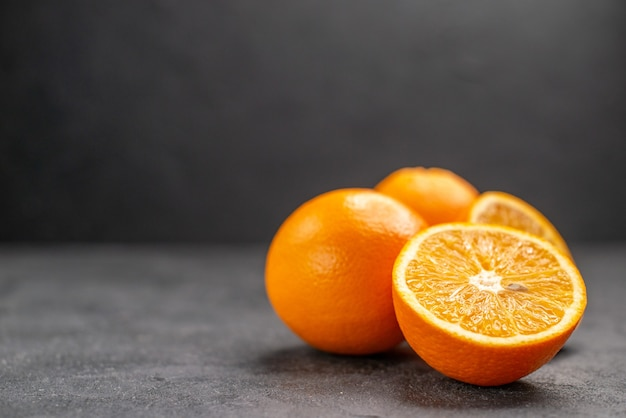 暗いテーブルの上の新鮮な全体とスライスされたレモンの水平方向のビュー