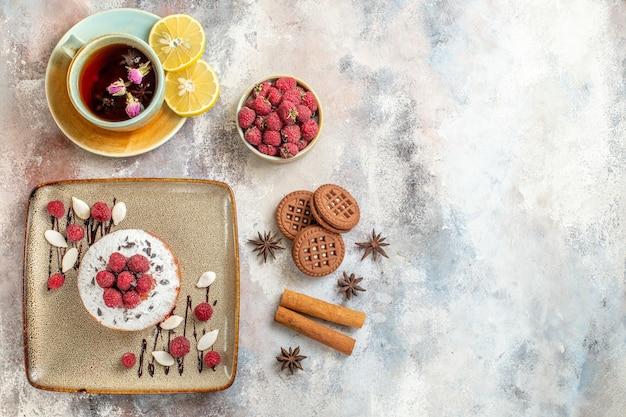 ラズベリーと焼きたてのケーキの水平方向のビューレモンシナモンライムと紅茶のカップ