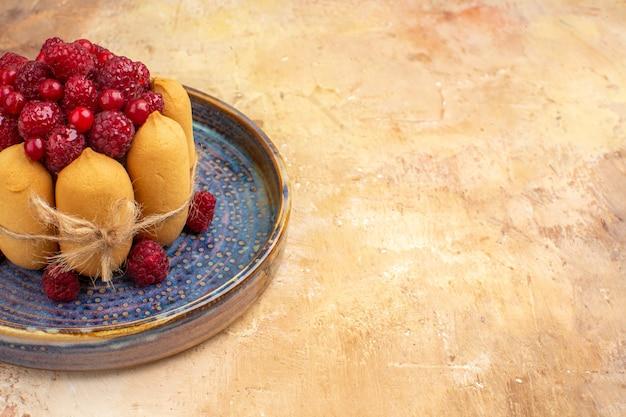 Горизонтальный вид свежеиспеченного подарочного торта с фруктами на столе смешанных цветов