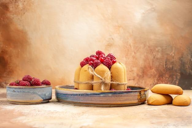 混合色のテーブルにフルーツとビスケットと焼きたてのソフトケーキの水平方向のビュー