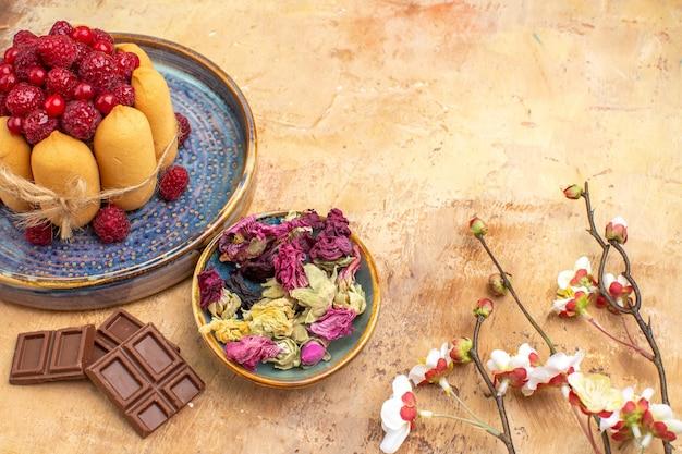 フルーツの花とチョコレートバーと焼きたてのソフトケーキの水平方向のビュー