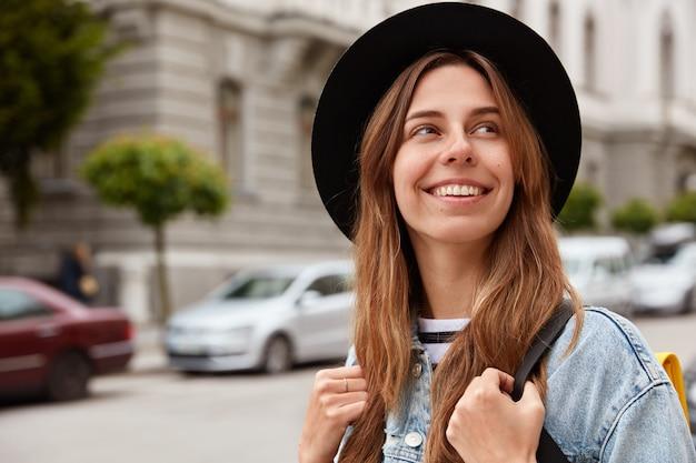 嬉しい笑顔の女性歩行者が通りを散歩し、幸せそうに目をそらしている水平方向のビュー