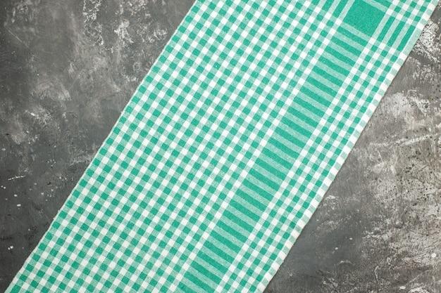 Горизонтальный вид зеленого полосатого полотенца на сером столе