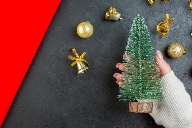 暗い背景の上の装飾アクセサリーとクリスマスツリーを持っている手の水平方向のビュー
