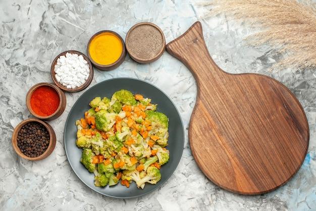 Горизонтальный вид здорового овощного салата, различных специй и разделочной доски на белом столе
