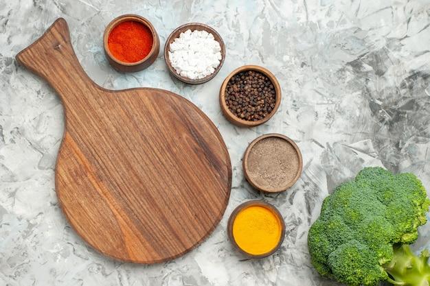 白いテーブルの上の健康な木製まな板さまざまなスパイスとブロッコリーの水平方向のビュー