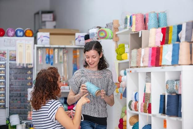 Горизонтальный вид помощника-помощника в розничном магазине, помогающего женщине купить клубок голубой пряжи
