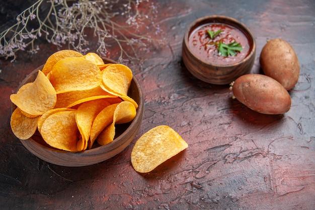 小さな茶色のボウルポテトと暗い背景のケチャップで自家製のおいしいポテトクリスピーチップスの水平方向のビュー
