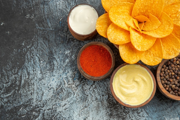 회색 테이블에 꽃 모양과 다른 향신료 마요네즈처럼 장식 된 수제 감자 칩의 가로보기