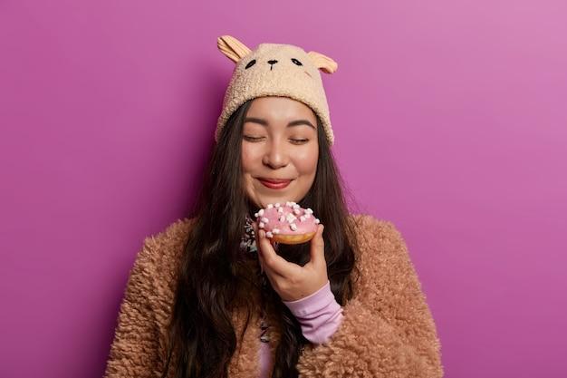 기쁜 표정으로 사랑스러운 여자의 가로보기, 눈을 감고 맛있는 도넛 냄새, 라일락 벽 위에 절연 겨울 의류를 착용