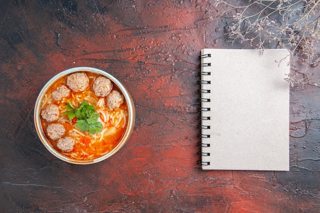 茶色のボウルに麺と暗い背景のノートブックとミートボールスープの水平方向のビュー