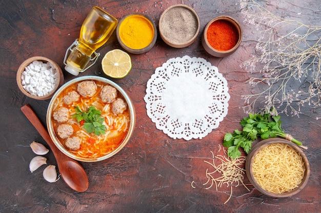 茶色のボウルレモンスプーンに麺とミートボールスープの水平方向のビュー暗いテーブルに緑のさまざまなスパイスとオイルボトルナプキンパスタの束