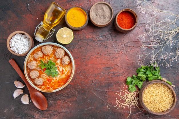 茶色のボウルに麺が入ったミートボールスープの水平方向のビューレモンスプーン暗いテーブルに緑のさまざまなスパイスとオイルボトルパスタの束