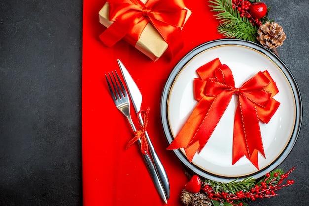 赤いナプキンのギフトの横にあるディナープレートカトラリーセット装飾アクセサリーモミの枝に赤いリボンと新年の背景の水平方向のビュー