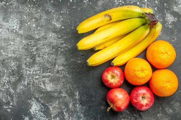 어두운 배경의 왼쪽에 있는 유기농 영양 공급원 신선한 바나나 묶음과 빨간 사과 오렌지의 수평 보기