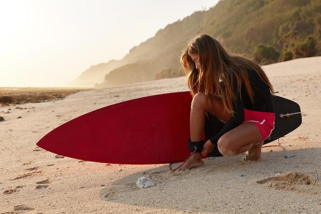 Горизонтальный вид профессионального сёрфбордиста, пристегивающего поводок под углом для безопасной борьбы с волнами