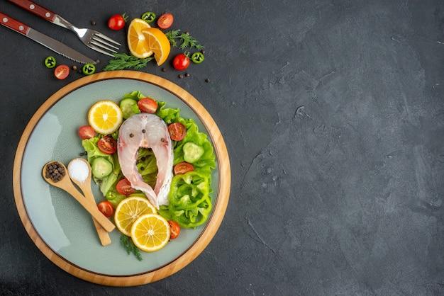 生の魚と新鮮なみじん切り野菜の横から見た図 レモン スライス スパイスを灰色の皿に置き、カトラリーを黒い表面の右側に置く