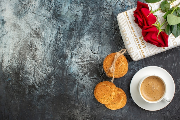 ギフトボックスとクッキーの赤いバラの水平方向のビューは、氷のような暗い背景の左側にコーヒーを1杯