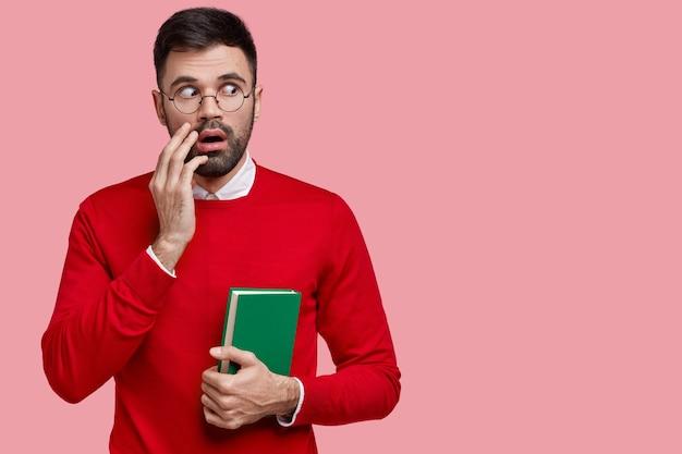 怖いひげを生やした男の水平方向のビューは驚くほど脇に見え、信じられないほどの何かに気づき、緑色のノートを持っています