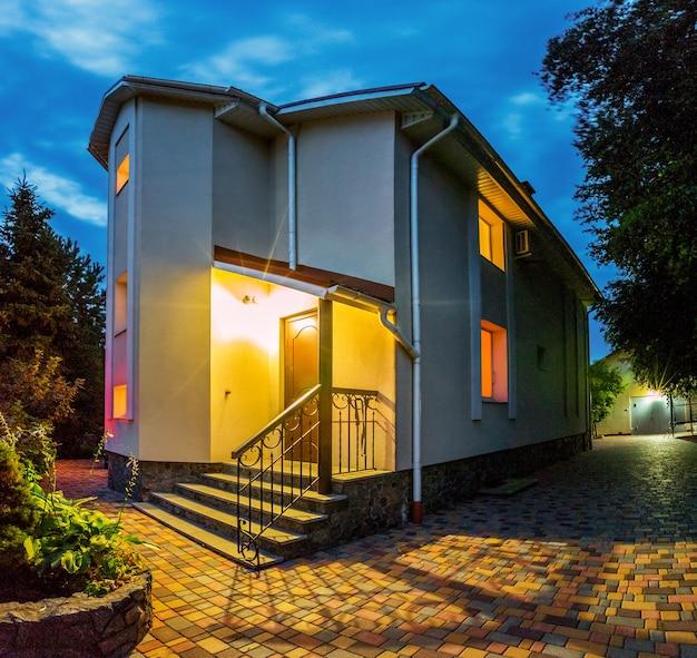 パティオ付き一戸建て住宅の水平方向のビュー。マンション。夕方の時間。窓からの黄色い光