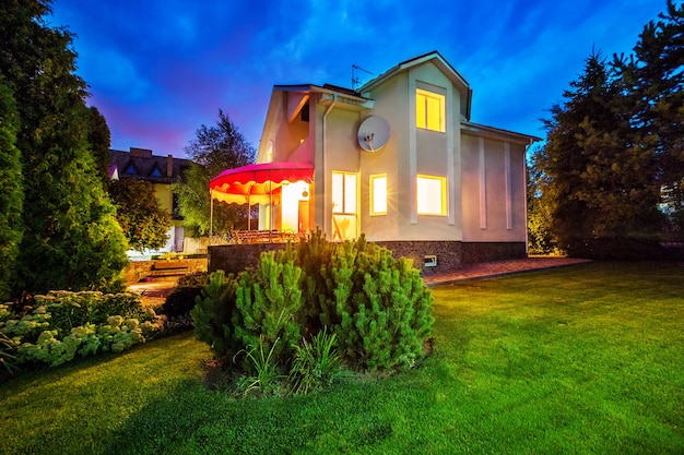 窓からのパティオの夜の時間黄色の光と一軒家の水平方向のビュー