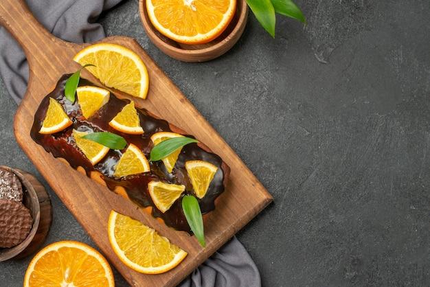 부드러운 맛있는 케이크의 가로보기는 나무 커팅 보드와 수건에 비스킷으로 오렌지를 잘라냅니다.