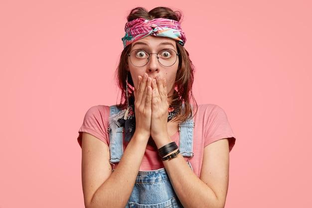 驚いた感情的な女性のヒッピーの水平方向のビューは、両手を口に保ち、目を悩ませています