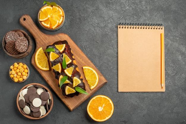 おいしいケーキの水平方向のビューは、暗いテーブルのまな板にビスケットとノートブックでオレンジをカットしました