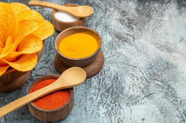 Горизонтальный вид вкусных картофельных чипсов, украшенных разными специями в форме цветов с ложками на сером столе