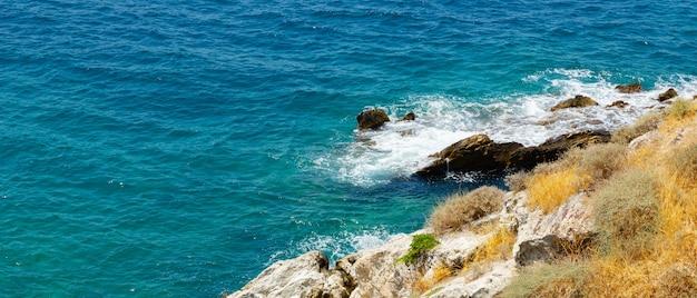 Горизонтальный вид на бирюзовые воды моря. дикие скалы перед бирюзовой водой. летний отдых у моря