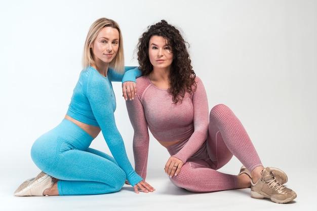서로 다른 체형을 가진 두 여성이 바닥에 앉아 함께 포즈를 취하는 모습을 가로로 바라보며 여성의 모습을 보여줍니다. 스포츠 및 레크리에이션 개념
