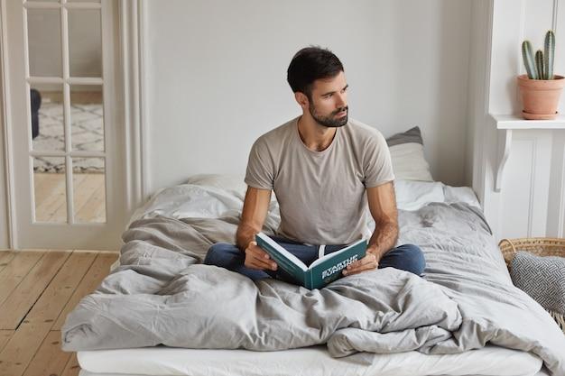 思いやりのあるひげを生やした男の水平方向のビューは、本を保持し、快適なベッドに足を組んで座っています