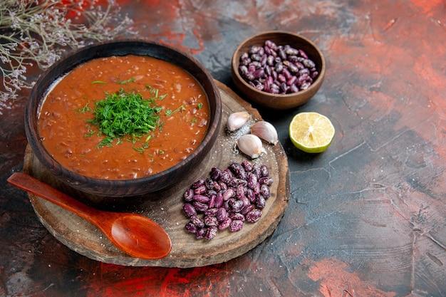 혼합 색상 테이블에 나무 커팅 보드와 숟가락에 토마토 수프 콩 마늘의 가로보기
