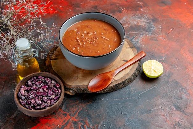混合色のテーブルの上のトレイ豆油瓶の青いボウルにトマトスープの水平方向のビュー