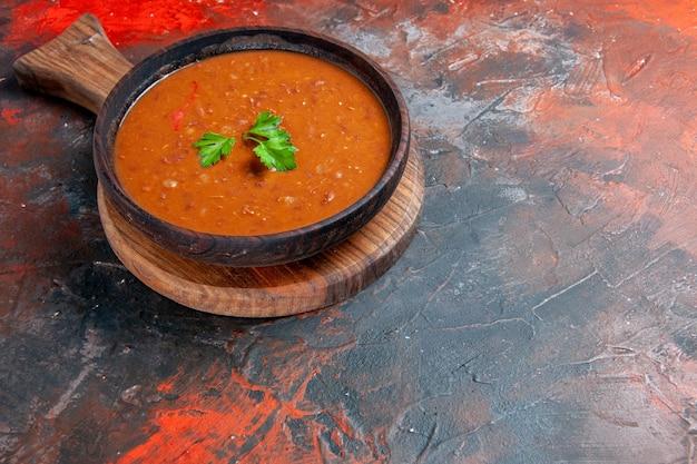 混合色のテーブルの右側にある茶色のまな板にトマトスープの水平方向のビュー