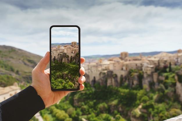 알아볼 수 없는 남자가 휴대전화로 유럽의 여행지에서 사진을 찍는 수평적 전망. 스페인 도시 쿠엥카의 기술, 관광 및 휴일 개념.