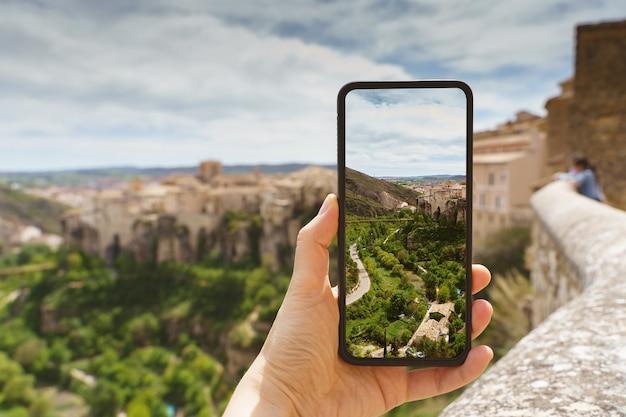 알아볼 수 없는 여성이 휴대전화로 유럽 여행지에서 사진을 찍고 있는 수평적 전망. 스페인 도시 쿠엥카의 기술, 관광 및 휴일 개념.