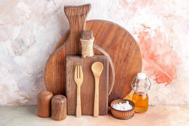 カラフルな壁にさまざまなまな板の木のスプーンの小さなオイル ボトルの水平ビュー