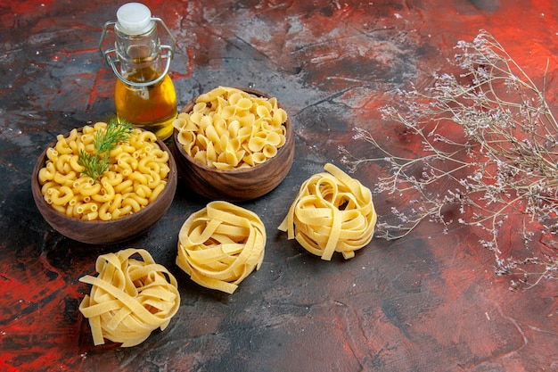 混合色のテーブル上のさまざまな種類の未調理のパスタとオイルボトルの水平方向のビュー