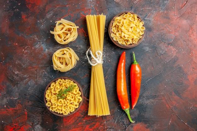 混合色のテーブル上のさまざまな種類の未調理のパスタとピーマンの水平方向のビュー