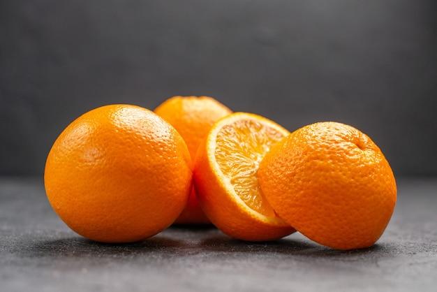 暗いテーブルの上の全体と刻んだ新鮮なレモンの水平方向のビュー