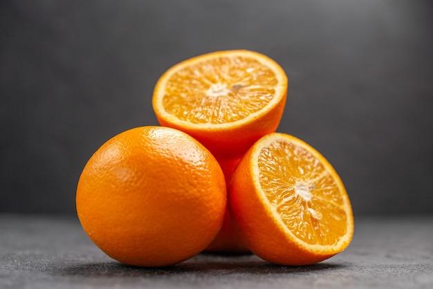 全体とみじん切りの新鮮なオレンジの暗いテーブルの水平方向のビュー