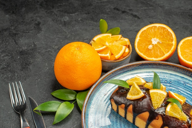暗いテーブルの上にフォークとナイフで黄色の全体とカットレモンのおいしいケーキの水平方向のビュー