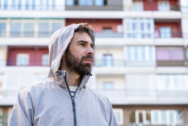 Горизонтальный вид молодого человека, изолированного перед небольшими дешевыми квартирами на открытом воздухе.
