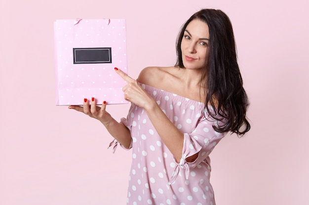 Horizontal view of pleasant looking european woman points at gift bag, shows free space for your advertising content or promotion, dressed in polka dot dress, has red manicure. isolated shot