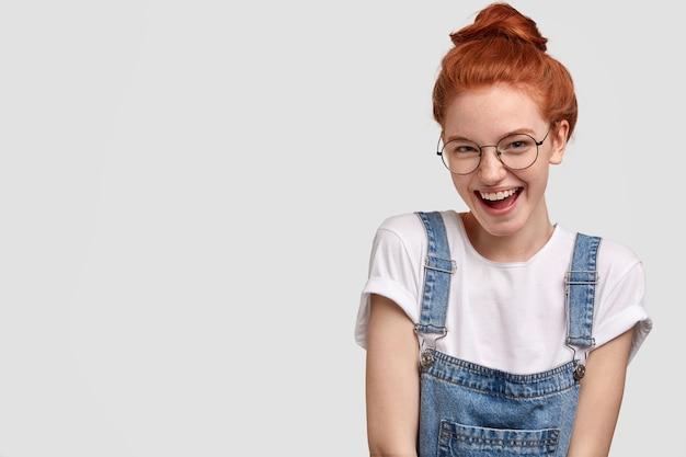 Vista orizzontale della ragazza lentigginosa felice con i capelli rossi, si sente soddisfatta come vestito nuovo raccolto dallo sconto, vestito con maglietta bianca e tuta in denim, modelli sopra il muro bianco