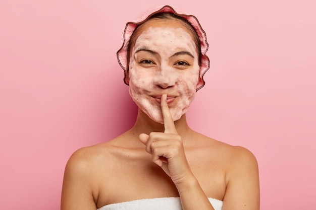 Horizontal view of pretty asian lady with foam on face, cleans from dirt, wants to have refreshed look, makes silence gesture, wears showercap, looks happily. cleanliness and hygiene concept