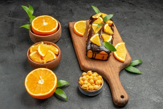 Vista orizzontale del set di taglio a metà affettato su pezzi di arance fresche torte morbide sulla tavola nera