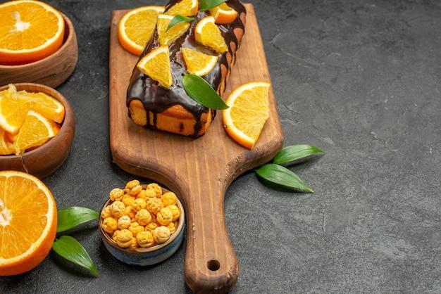 Vista orizzontale del set di taglio a metà affettato su pezzi di arance fresche e torte morbide